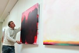 Kuraattori Markku Haanpää asettelee paikoilleen taiteilija Sini-Meri Hedbergin teoksia. Hedbergin maalaustapa on nopea ja työstämisen alkuvaiheessa häntä innoittaa sattuma.