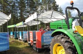 Tiedottaja Minna Kylälehtonen ja näyttelypäällikkö Jukka Isotalo istuvat messujunassa, joka kuljettaa näyttelyvieraita ympäri 23 hehtaarin näyttelyaluetta.