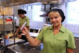 Riitta Etutalo esittelee lämpömittarin 30 asteen lukemia. Kivennäisvettä riittää, mutta hygieniasyistä vaatteita ei keittiössä voi vähentää. Taustalla Heidi Karjalainen pilkkoo sipuleita. Kuva: Kenneth Sundberg