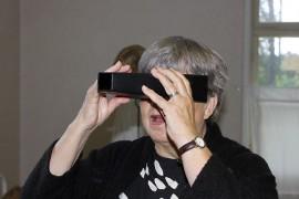 Eeva Virtanen tutkailemassa laitteella, jolla katsottiin ennen vanhaan röntgenkuvia