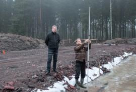 Mika Mäkinen seuraa, kuinka Seppo Herttuainen merkitsee tulevan hallin paalupisteitä. Kitkapaalut ulottuvat 15 metrin syvyyteen.