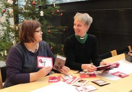 Mervi Kanniainen ja Minna Majuri-Kiiski ihailevat Pöytyän diakoniakerhon eläkeläisten  tekemiä joulukortteja. Joulumyyjäisissä myytävien korttien tuotto käytetään diakoniatyöhön.