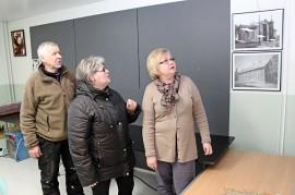 Hannu Kauti, Hilkka Palomäki ja Eija Kauti silmäilevät Ostarin seinillä olevia tauluja, joihin on ikuistettu vanhan Mellilän monia kohteita.
