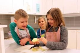 Ville Viitanen, Elsa Jalonen ja Eerika Lehtonen pohtivat, miten sipuli pilkotaan.