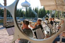 Konsertissa Pöytyän Puhaltajat soittaa Kyösti Iitin rakentamalta laululavalta. Yleisö kuuntelee lammen toisella puolella.