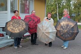 Antaa sateen tulla: me olemme valmiit. Sinikka Naaranoja, Maija-Liisa Meronen, Eeva Kojola ja Eeva-Liisa Rönnemaa esittelevät uudistettuja sateenvarjojaan.
