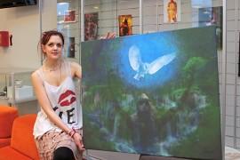 Sari-Anna Lämsä esittelee teoksensa Disconnect your humanity, jota voisi äkkiseltään luulla maalaukseksi.