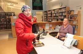Turussa työssä käyvälle Saija Mattilalle on tärkeää, että kirjastoon pääsee jatkossakin illalla. Lainauspöydän takana on kirjastovirkailija Kirsi Mäntylä.
