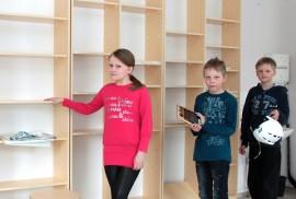 Kolmasluokkalaiset Jasu Nieminen, Katariina Auranen ja Miika Aaltonen esittelevät tyhjiä kirjahyllyjä.