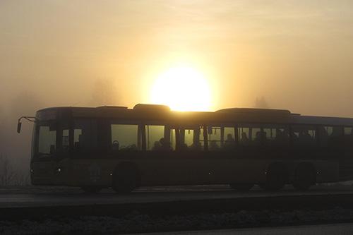 Risto K:n kuvassa aurinko laskee paikallisliikenteen linja-auton taakse sumuisessa illassa.