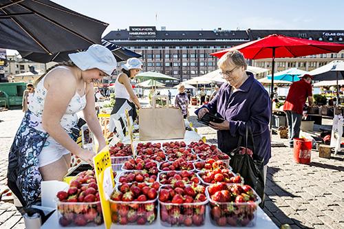 Leila Storgård (oik). osti keskiviikkona ensimmäiset mansikat pakastimeen. Sanni Ristolainen myi pöytyläisen Raikon marjatilan marjoja. Kuva: Riitta Salmi.